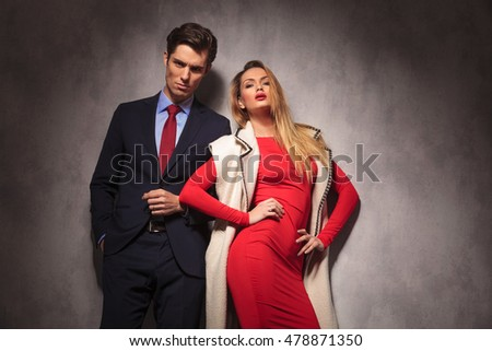 provocative blonde woman in red dress posing near her lover dressed in suit and tie
