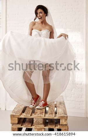 Provocative bride in wedding dress and red sneakers smiling happy, lifting up dress.
