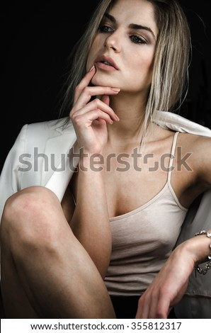 Provocative girl sitting in the dark on a chair in their underwear with white jacket