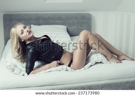 provocative lady with perfect body and long blonde hair lying on bed with black panties and sexy leather jacket. Erotic expression, sensual pose  - stock photo