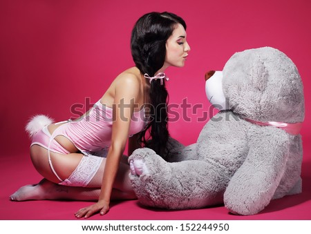 Provocative Playful Woman in Pink Lingerie kissing Big Soft Toy - Teddy Bear - stock photo