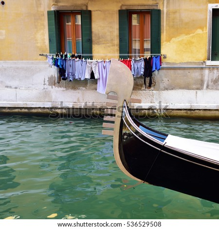 Prow of the gondola on the Venetian water canal with and handing linen on background colorful facade. Venice, Italy