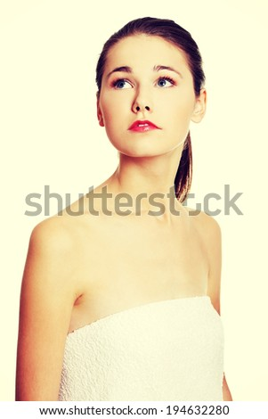 Prtrait of a young beautiful female caucasian teen looking up to the site, being wrapped with a towel