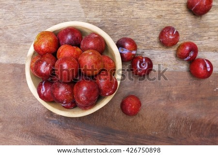 Prune in wooden  bowl on wooden texture , selective focus . - stock photo
