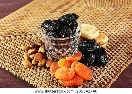 Prunes and other dried fruits on wicker mat, closeup - stock photo