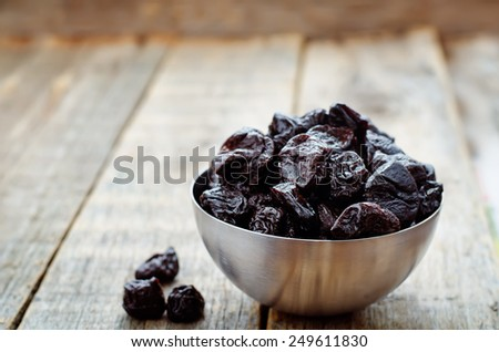 prunes in a bowl on a dark wood background. tinting. selective focus - stock photo