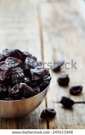 prunes in a bowl on a dark wood background. tinting. selective focus