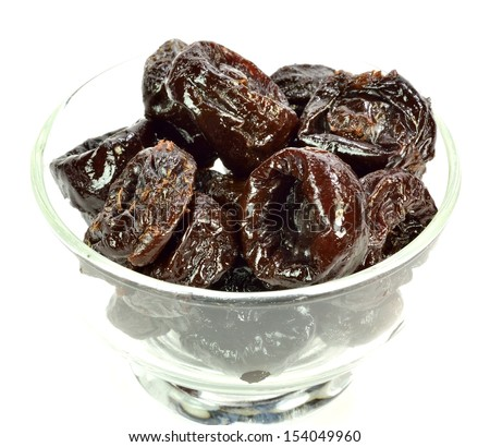 Prunes in a glass bowl on a white background.