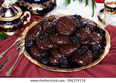 prunes in chocolate candy in a dish dishes still life expensive antiques beautiful elegant sophisticated tasty appetizing - stock photo