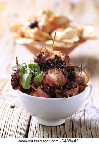 Prunes wrapped in rashers of bacon - stock photo