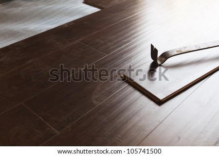 Pry Bar Tool with New Laminate Flooring Abstract. - stock photo