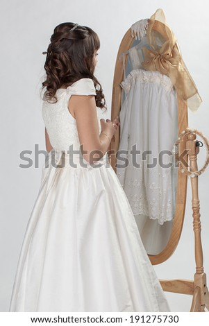 prying girl going to the first holy communion - stock photo