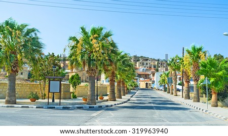 PSEMATISMENOS, CYPRUS - AUGUST 4, 2014: The street with green palms leads to the old village centre, on August 4 in Psematismenos, Cyprus.