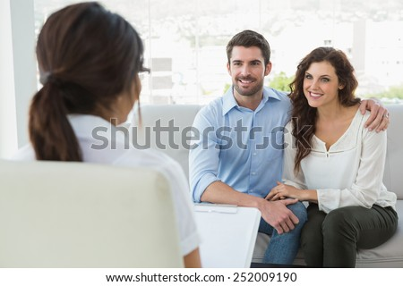 Psychiatrist listening her smiling patients in the office - stock photo