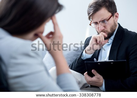 Psychiatrist talking with despair businesswoman in his office - stock photo