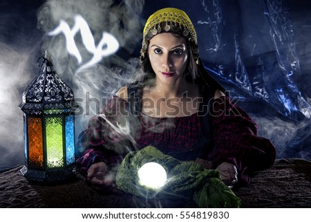 Psychic or fortune teller with crystal ball and horoscope zodiac sign of Capricorn, birthdays of December to January. The image depicts astrology in a mystical, esoteric or magical theme composite.