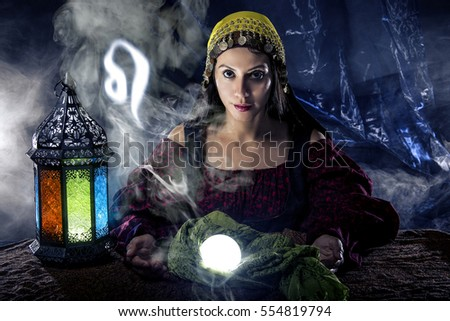 Psychic or fortune teller with crystal ball and horoscope zodiac sign of Leo, birthdays of July to August.  The image depicts astrology in a mystical, esoteric or magical theme composite.