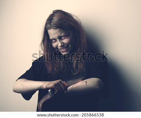 Psycho girl possessed by a demon with knife - stock photo