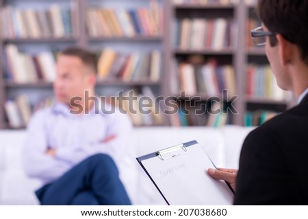 Psychologist having session with his depressed patient, close up - stock photo