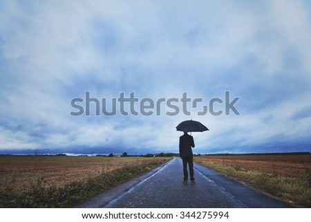 psychology concept, man with umbrella standing on the road, fears and solitude - stock photo