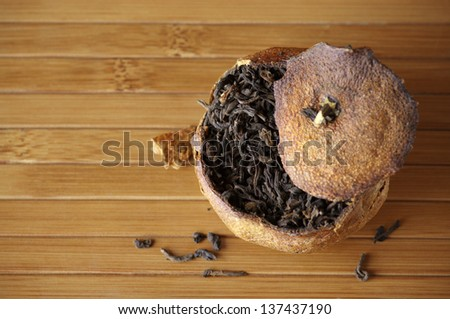 Pu-erh tea aged in tangerine on bamboo background. Top view point. - stock photo