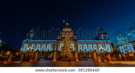 Public building in Belfast with christmas lights at night time with the moon on top of the building - stock photo