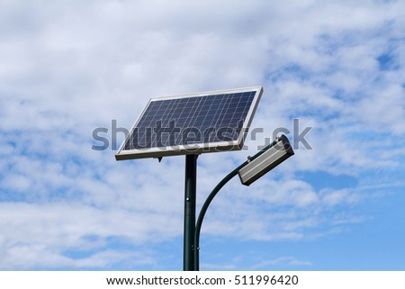 Public city light with solar panel powered on blue sky with clouds