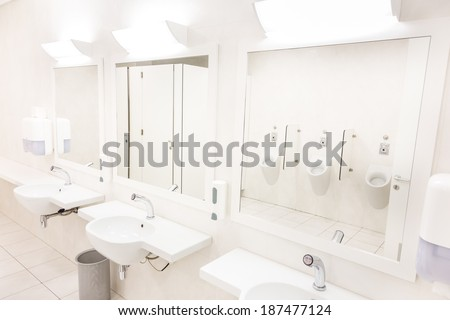 Public empty white man restroom with washstands mirrors. - stock photo
