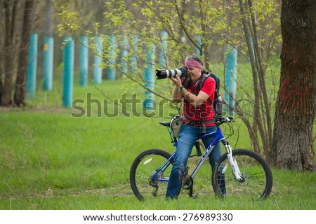 Public event to clean parks of the city of Kiev Ukraine. A man on a bicycle  and professional camera 04/25/2015 Trukhanov Island - stock photo