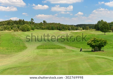 Public green golf course and blue cloudy sky. Field with trees landscape. Sunny day - stock photo