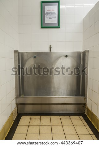 Public men's stainless steel urinal trough in tiled  bay.
