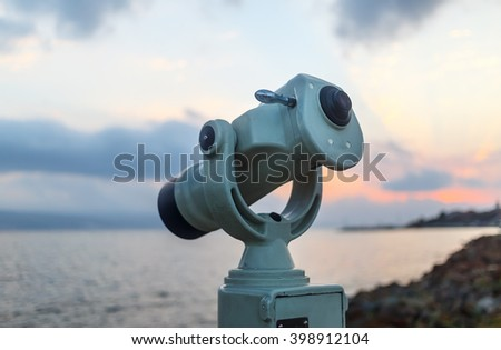 Public monocular on sea shore. Coin operated binocular viewer on blurred background of sunset and sea. Shallow depth of field. Selective focus. - stock photo