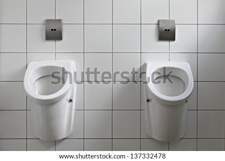 Public toilet interior with pissoirs - stock photo