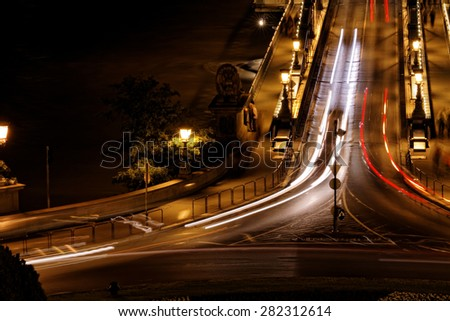 Public transport on the Suspension Bridge at night in Budapest - stock photo