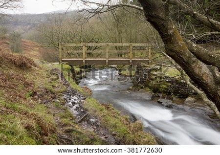 Public Walking Bridge. A bridge spans the gushing waters of a river on a nature trail in the Brecon Beacons national park in Wales.
