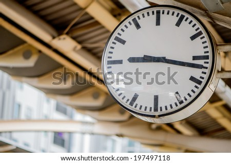 Public white round,circular  clock In a railway station perspective ,roof station train background blur 9:17 am,pm