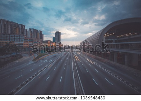 Puchong,Malaysia - 1 March 2018: Sunset view and night trails of busy traffic and Light Railway Transit station on the right side. The image may has blurred effect and soft focus due to long exposure.