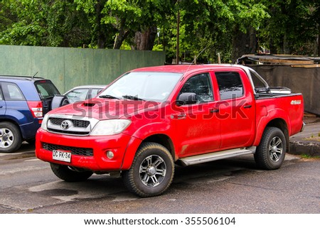 PUCON, CHILE - NOVEMBER 20, 2015: Red pickup truck Toyota Hilux at the town street. - stock photo