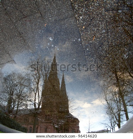 puddle in freiburg with reflection of church - stock photo