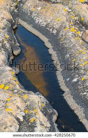 Puddle in rock formations at the Baltic shore, Grisslehamn - stock photo