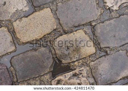 Puddles of water from rain on wet cobblestone road  - stock photo