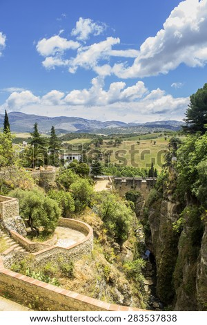 Puente Viejo, Old Bridge, also known as Arab Bridge. The oldest and smallest of three bridges that span the 120-metre deep chasm that carries Guadalevi­n River and divides the city of Ronda in Spain. - stock photo
