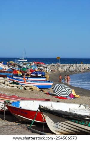 PUERTO BANUS, SPAIN - SEPTEMBER 14, 2009 - Colourful Spanish fishing boats on the beach with holidaymakers sunbathing, Puerto Banus, Marbella, Costa del Sol, Andalusia, Spain, September 14, 2009. - stock photo