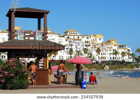 PUERTO BANUS, SPAIN - SEPTEMBER 14, 2009 - Holidaymakers at a snack bar on the beach with the Hotel Park Plaza Suites to the rear, Puerto Banus, Marbella, Andalusia, Spain, September 14, 2009. - stock photo