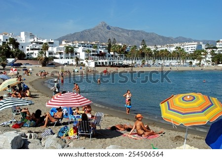 PUERTO BANUS, SPAIN - SEPTEMBER 14, 2009 - Holidaymakers relaxing on Playa de Nueva beach, Puerto Banus, Marbella, Costa del Sol, Malaga Province, Andalusia, Spain, Western Europe, September 14, 2009. - stock photo