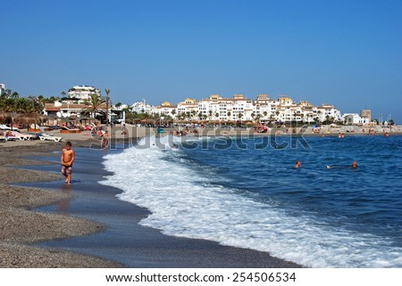 PUERTO BANUS, SPAIN - SEPTEMBER 14, 2009 - Holidaymakers relaxing on the beach and in the sea with the Park Plaza Suites Hotel to the rear, Puerto Banus, Marbella, Spain, September 14, 2009. - stock photo