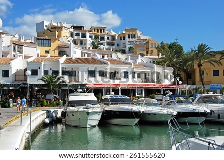 PUERTO CABOPINO, SPAIN - JUNE 7, 2009 - Boats in the inner harbour with apartments and restaurants to the rear, Puerto Cabopino, Costa del Sol, Malaga Province, Andalusia, Spain, Europe, June 7, 2009. - stock photo