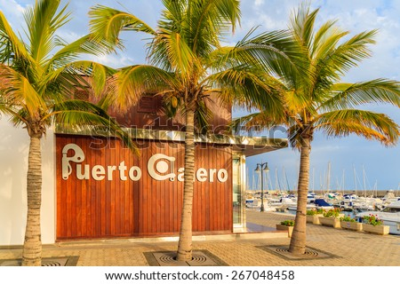 PUERTO CALERO MARINA, LANZAROTE ISLAND - JAN 12, 2015: marina building and palm trees in Puerto Calero port built in Caribbean style. This is modern yacht marina which is visted by many tourists. - stock photo