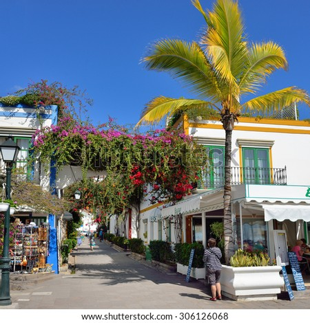 PUERTO DE MOGAN, GRAN CANARIA - FEB 19, 2014: Street with white houses colonia shown in Puerto de Mogan, Spain.  Favorite vacation place for tourists and locals on island. - stock photo