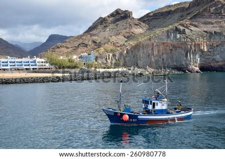 PUERTO DE  MOGAN, SPAIN - FEBRUARY 13;  Colorful canarian fishing boat enters  the harbor at Puerto de Mogan at the island Gran Canaria in Spain.  Photo taken on February 13, 2015  in Mogan, Spain. - stock photo